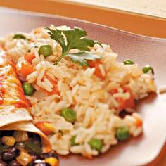 Quick Spanish Rice Recipe1 cup uncooked long grain rice 2 tablespoons canola oil 1 small onion, chopped 1 garlic clove, minced 1/2 teaspoon salt, optional 1 cup water 1 cup chicken or vegetable broth 2 large tomatoes, peeled and chopped 1/3 cup frozen peas, thawed 1/3 cup diced cooked carrots