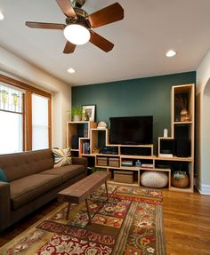 contemporary family room, teal accent wall, recessed ceiling lights, floral patterned area rug, prairie style stained glass, custom upholstery, media solution