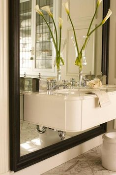 Julie Charbonneau   House & Home Mag    contemporay wall-mounted sink with black beveled floor mirror and floating white carrara marble vanity sink.