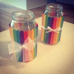 Turn and old jar into a colourful pencil holder or vase. Glue a strip of paper around your jar (the popsicle sticks hold better to the paper than the jar), glue your coloured popsicle sticks around the jar.. Then tie a ribbon around it. This is a really easy craft, that looks good and is great for kids!