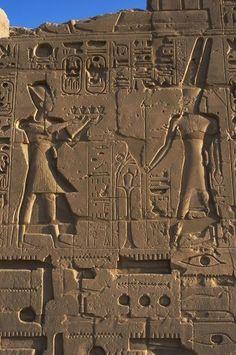 """Bajorrelieve representando a RAMSES II con el tocado ceremonial azul """"Khepresh"""" portando una bandeja de ofrendas al dios AMON con una corona de dos largas plumas segmentadas. Dinastía XIX del Imperio Nuevo. TEMPLO DE KARNAK muy cerca del situado en Luxor."""