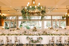 Eucalyptus-and-Bay laurel garlands decorating chandeliers and head table. A mixture of alternating square and round tables are covered with textured linen and have centerpieces of the same flowers