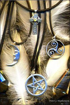 A moon, pentacle, triskele, and Celtic cross flanked by scrying crystals on feathers and fur.