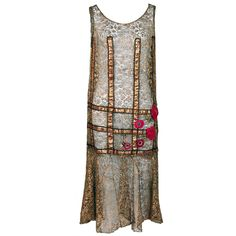This is an extraordinarily beautiful and exceptional 1920s metallic-lace & lame dance dress. It is embellished with magenta-pink velvet roses, whose texture creates a dazzling 3-D effect. The effortless drop-waist shape really allows one to appreciate the treasure trove of antique textiles. The dramatic criss-cross lame detail really sets this garment apart from other flapper dresses of the time.