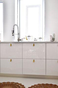 White kitchen, white floor, yellow leather handles, jute doilie rugs, Elke van den Berg design ceramic