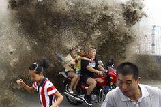 Varios turistas intentan alejarse de una ola gigante provocada por el viento en el río Qiantang, China. 13 de agosto. Foto: Reuters