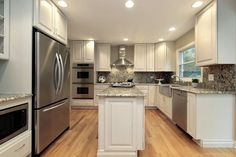 A white kitchen with a long, narrow kitchen island and countertops that match the backsplash.