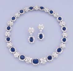 A SAPPHIRE AND DIAMOND NECKLACE AND EARRINGS   The necklace comprising fifteen graduated sapphire and diamond clusters to the pear and brilliant-cut diamond star shaped spacers and clasp, earrings en suite, 40.8 cm