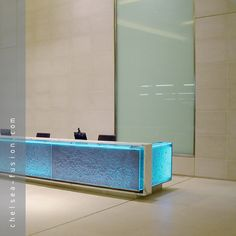Whether bespoke or standard patterns, kiln formed #glass gives a unique beauty, subtlety and tactile quality and can be used both decoratively and structurally. A wide range of surface finishes including sandblasting, etching/frosting, transparent and opaque colours and mirroring can further enhance these textures. Image: Our kiln formed/cast glass lit with coloured light and used for a desk front. The glass is translucent with a bespoke pattern and texture. #architecture
