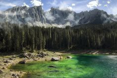"Huub wolfs photography posted a photo:  Lake Carezza, ""Rainbow lake"" at the foot of the Latemar.  In western Dolomites, only six kilometres from Nova Levante, there is a small, emerald green mountain lake, in which the Catinaccio and Latemar are reflected: lake Carezza. Due to its impressing colours, in Ladin language it is called ""Lec de Ergobando"" (rainbow lake). But its colours are not the only reason…  According to legends, once upon a time there was a beautiful mermaid living in the…"