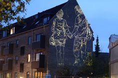 Asbjørn Skou (1984) woont en werkt in Kopenhagen, waar hij allerlei soorten afbeeldingen en tekeningen creëert en soms ook lichtinstallaties. Het beeld op de foto is van een serie uit 2010 Markeringer, waarbij etsen op een treinstation geprojecteerd werden. Wat mij aanspreekt is dat het net lijkt of de afbeelding in het gebouw is geëtst, waardoor het licht uit het gebouw naar buiten lijkt te kruipen.