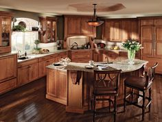 Mom likes this hood.  Curved lines and multiple counter heights add architectural dimension in this L-shaped kitchen with a rounded island.