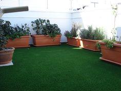 terraza con cesped artificial maceteros y plantas