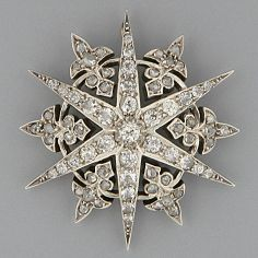 A diamond star brooch The six rayed star set with brilliant, old, mine and rose-cut stones interspaced with fleur de lys motif between, screw brooch fitting, soldered ring for pendant mount, 43mm diameter.