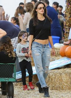 Supermodel chic: Ale displayed her toned and tanned midriff in low-slung distressed boyfriend jeans and a cropped black top, paired with black ankle boots as she was followed closely behind by her mini-me