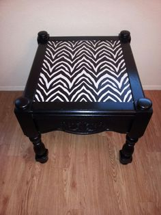 End table repainted in a high gloss black paint with black and white zebra print contact paper.
