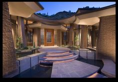 Absolutely stunning entry way! Water feature, round, welcoming doors, well lit, foliage. Perfection