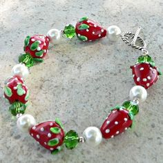Wear this fresh-as-spring bracelet of luscious strawberries, perfect glass pearls, and green faceted glass beads and enjoy! The bracelet fits