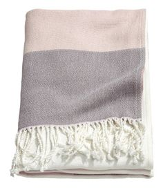 Dusky pink. Color-block throw in a woven cotton blend with twisted tassels along short sides.