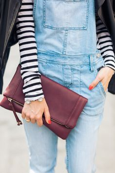 This burgundy foldover clutch elevates a casual outfit.