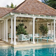 poolside pavilion, aluminum outdoor furniture in a playful light turquoise color by Janus et Cie complements the blue water.