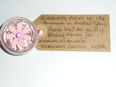 Pillsbury's Pieces No, 192. Pin with pale pink metallic capsule with  pink flower. In exchange for a donation to KATHMANDU ANIMAL TREATMENT CENTRE, Nepal. Available at St. George's Church, Madrid on Saturday 13 June from 11.00 - 15.00.