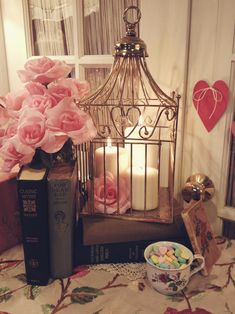 vignette with birdhouse, candles, books, roses, tea cup and heart.