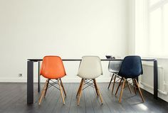 off-white walls, dark wood floors and mismatched eames plastic chairs