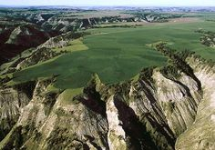 "Badlands Grain Fields in Montana;  photo by William Albert Allard;  ""Grainfields spill their color across the badlands of the Missouri Breaks, a lonesome swatch of eastern Montana where the Great Plains roll to an abrupt and wild end. The Missouri River and its tributaries have cut deep paths through underlying sandstone and shale, fracturing the open country.""   —From ""The Missouri Breaks,"" May 1999, National Geographic magazine"