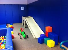 The back corner of the gym has our slide with soft blocks for building and crashing, with our stepping stone buckets and balance beam behind the ball pit.