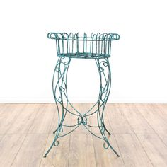 This shabby chic plant stand is featured in a wire metal with a distressed light blue patina finish. This planter stand has a round pot holder top, curved legs and swirl accents. Perfect for an outdoor patio or garden! #shabbychic #tables #plantstand #sandiegovintage #vintagefurniture