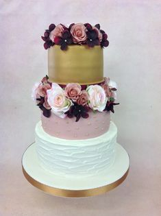 The perfect three tier wedding cake which features beautifully delicate blousy roses, textured royal icing and a metallic gold top tier.