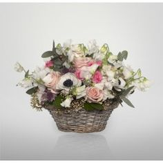 A handpicked basket of pretty pastel coloured flowers that include white sweet peas, sweet avalnche roses, anemones and astrantia