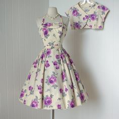 A refreshing white and orchid colored rose print is fashioned into a lovely 1950s sundress with matching bolero...