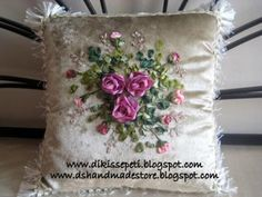 It's a stitched and embroidered pillow with silk ribbons on velvet. On the spaces between embroideries, it also has beadwork.  You can see more patterns