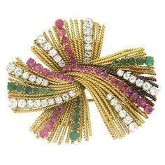 An 18k yellow gold brooch set with approximately 2.50ctw in G-H/VS-SI1 diamonds, rubies and emeralds DESIGNER: Not Signed MATERIAL: 18K Gold GEMSTONE: Diamond, Ruby, Emerald DIMENSIONS: The brooch mea