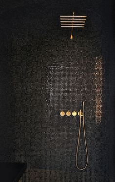 CONTEMPORARY vibe from black mosaic tiles cantilevered black seat simple lines minimalist look. GLAM factor from glossy-finished gray mosaic tiles that reflect light gold-finished rain shower & shower controls.