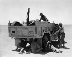 """THE LONG RANGE DESERT GROUP (LRDG) DURING THE SECOND WORLD WAR part of """"THE BRITISH ARMY 1939 - 1945: THE LONG RANGE DESERT GROUP"""" (photographs) A Long Range Desert Group truck halted while its crew enjoy a midday break in the shade beneath the vehicle, July 1942. This shade was sometimes shared by exhausted and migrating birds. Corporal Read, Medical Orderly, is on top of the truck. It was..."""