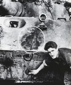 An individual pointing out the many anti tank hit marks on this King Tiger