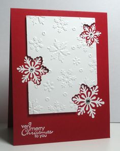 handmade Christmas card from Think Outside the Box: Snowy Christmas Greetings ... panel with embossing folder snowflakes .. off the edge negative space snowflakes with complete snoflackes on base layer ... red and white ... great card!!