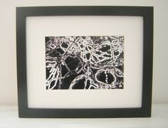 Black and white negative print of snow capped branches. Art photography,art gifts,home gifts,original gifts,luxury gifts,mens gifts,womens gifts, affordable art,framed photography,Off white mount, backed. Black thick frame which can either be hung onto a wall or placed on a flat surface. There is a stand at the back of the frame. Approx 11 x 9 inches ( 29cm x 24cm) One of a kind