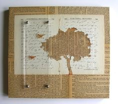 birds and tree negative die cut from aged white paper over yellowed book/newspaper.