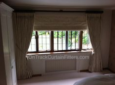 63mm Wooden pole and Roman blind fitted by OnTrackCurtainFitters.com. Curtains hung and dressed as standard and then steamed for beautiful finish.