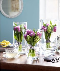A bunch of purple tulips standing in three vases