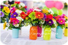 Colorful daisy centerpieces in painted mason jars Mexican Fiesta Party, Fiesta Theme Party, Mexican Fiesta Decorations, Party Themes, Daisy Centerpieces, Mexican Wedding Centerpieces, Colorful Centerpieces, Centerpieces With Mason Jars, Mason Jar With Flowers
