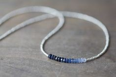 This delicate necklace is made up of silver tone charlotte cut seed beads, and a segment of shaded blue sapphire rondelles. Charlotte cut seed