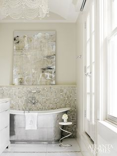 Courtney Giles Bathroom | A freestanding nickel tub, a sparkling chandelier hung from an arch-top ceiling and showstopping art by Susanne Carmack creates a glamorous but serene master bath.