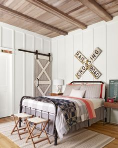 "A salvaged crossing sign above 3-year-old Collier's antique iron bed honors his hometown's history as a railroad town. Elements like an antique barn door and cedar fence boards (from the Crouches' last home) planked on the ceiling allow for an eventual ""express transfer"" from little boy room to tween hangout."