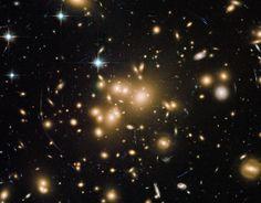 """Abell 1689. No son estrellas, sino galaxias, con miles de millones de estrellas cada una. La foto la hizo el Hubble. La masa del cúmulo es tal, que curva el espacio circundante y desvía los rayos de luz que atraviesan la región, procedente de objetos más distantes. Es lo que los científicos llaman una """"lente gravitacional"""". Sin embargo, de toda esa masa, sólo el 1% corresponde a las galaxias que vemos. El resto es materia oscura."""