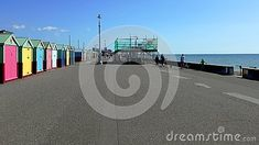 Colorful beach huts on Hoves promenade with scaffolding in background, East Sussex, England.